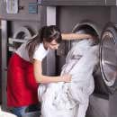 A woman pulling laundry from the dryer
